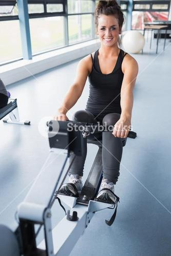 Happy brunette training on row machine