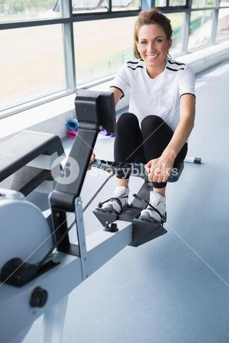 Happy woman on rowing machine