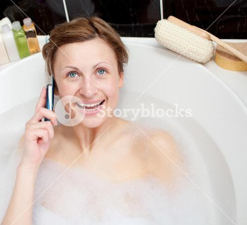 Bright woman talking on phone in a bubble bath