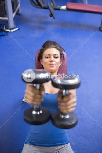 Woman straining to lift weights