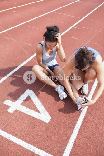 Woman caring about runner with sports injury