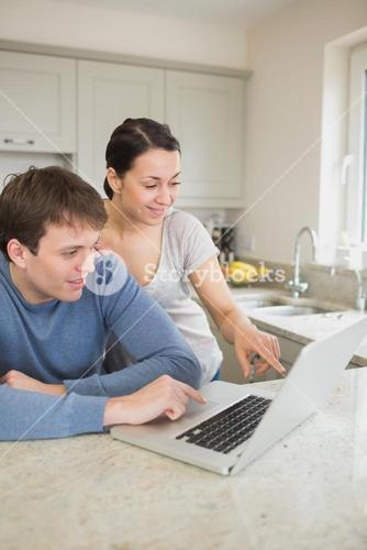 Happy couple looking at laptop