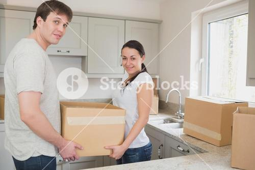 Young couple in the kitchen holding moving boxes