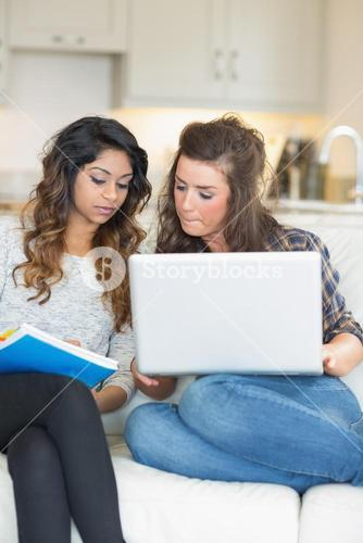 Girls doing homework with laptop