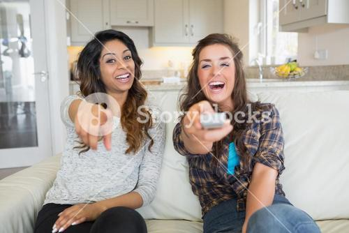 Two women smiling and laughing at television