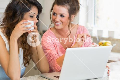 Girls chatting over coffee with laptop