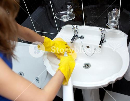 Woman cleaning a bathrooms sink