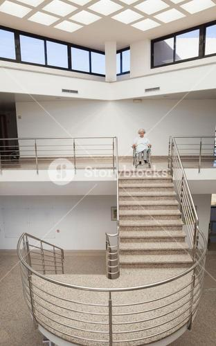 Elderly lady in wheelchair at top of stairwell