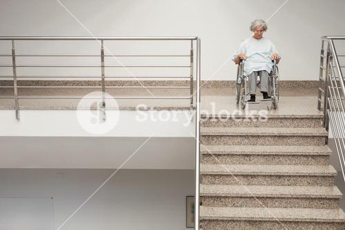 Elderly lady in wheelchair at top of stairs