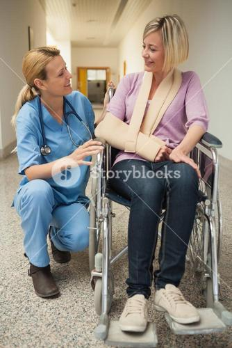 Nurse talking with patient in wheelchair with arm in sling