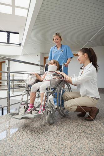 Mother crouching next to her child in wheelchair with nurse pushing it