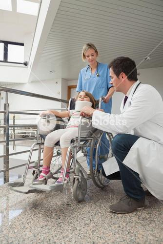 Doctor crouching next to child in wheelchair with nurse pushing it
