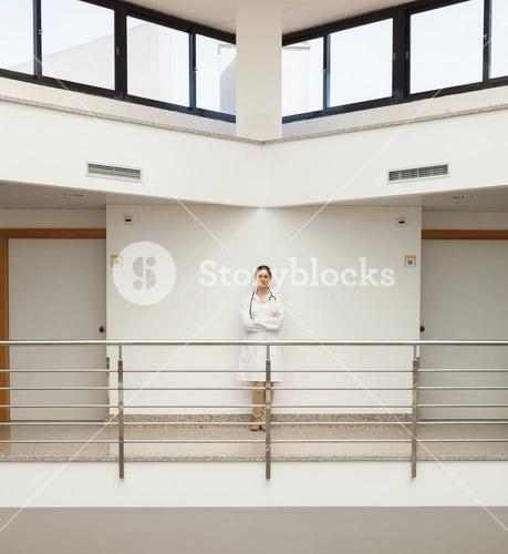 Female doctor standing against wall by stairwell