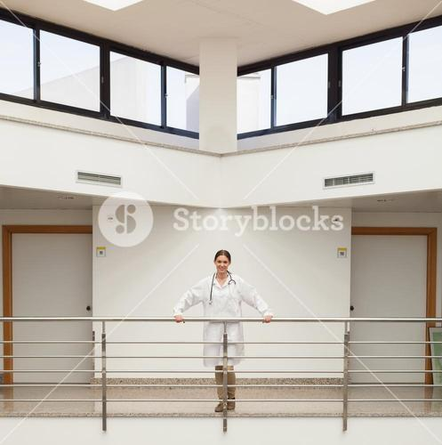 Smiling female doctor leaning on the railing