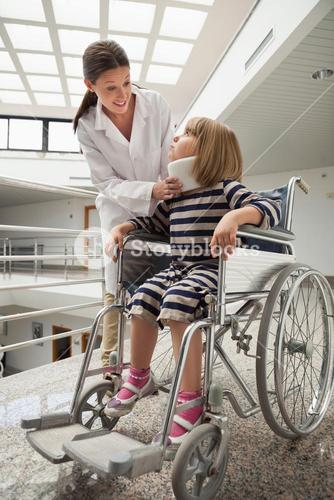 Doctor talking to child with neck brace in wheelchair