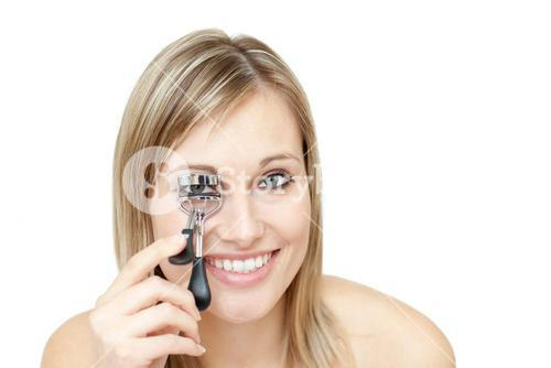 Lively woman holding an eyelash curler