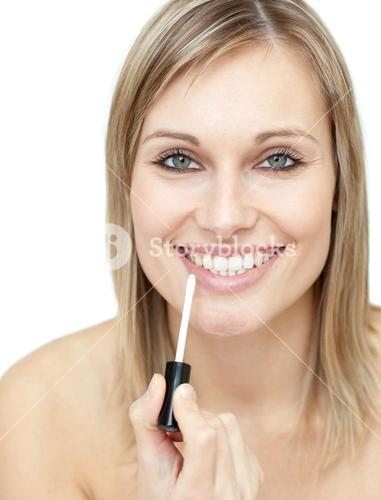 Smiling woman putting gloss
