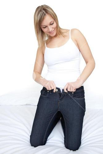 Charming woman putting on tight jeans on a bed