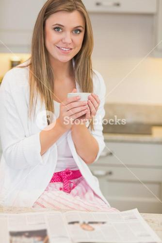 Woman in pyjamas with hot beverage