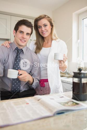 Couple drinking coffee together while reading newspaper