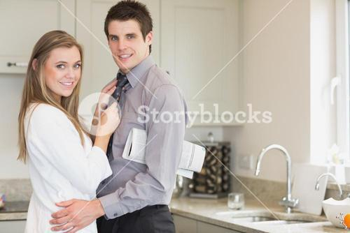 Man with a newspaper under his arm hugging his wife