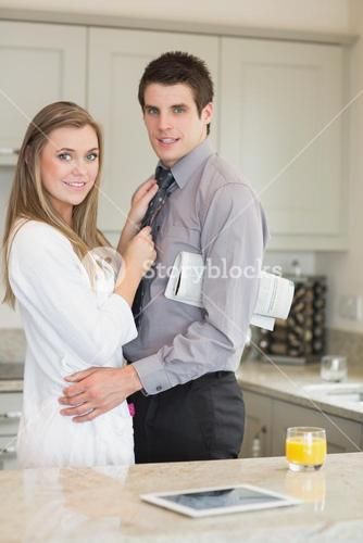 Woman hugging her husband with a newspaper under his arm