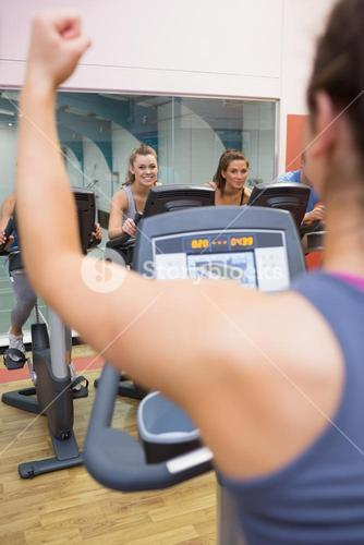Motivational female instructor teaches spinning class