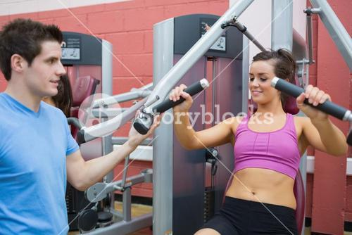 Woman using weights machine with trainer