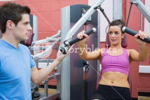 Trainer helping woman on weights machine