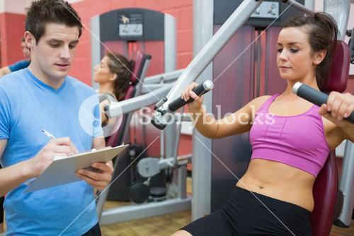 Trainer taking notes on client on weights machine