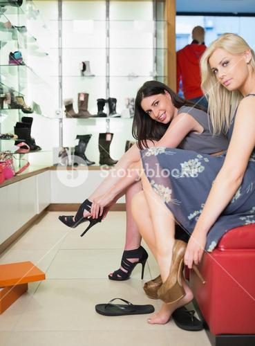 Women trying on shoes in shoe store