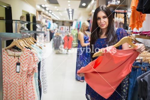 Woman in clothes shop looking at clothes