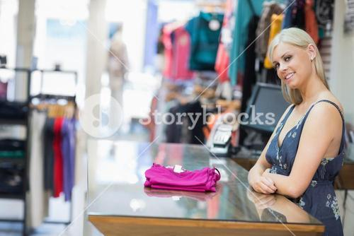 Woman smiling behind counter with folded clothes