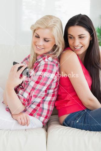 Women smiling looking at cell phone