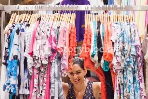 Woman crouching behind a clothes rack smiling