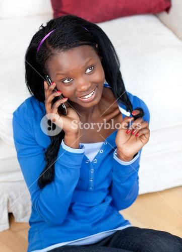 Attractive woman talking on phone in the livingroom