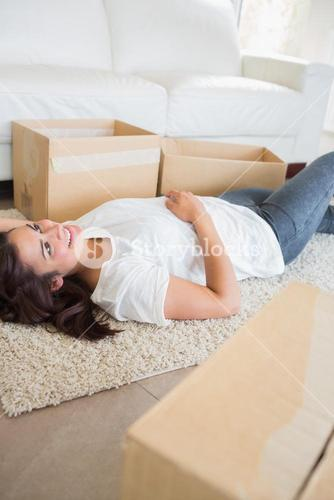 Woman lying on the carpet next to moving boxes