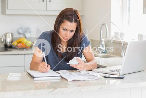 Woman calculating bills in the kitchen