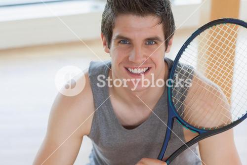Happy man holding a tennis racket