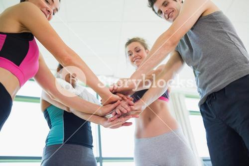 People putting hands together at the gym