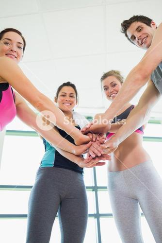 People putting hands together smiling