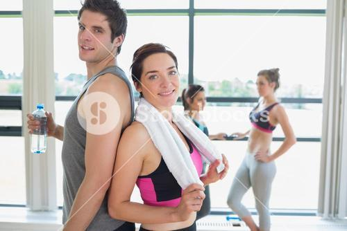 Man and woman standing back-to-back at the gym