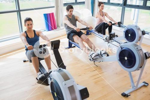 People using rowing machines