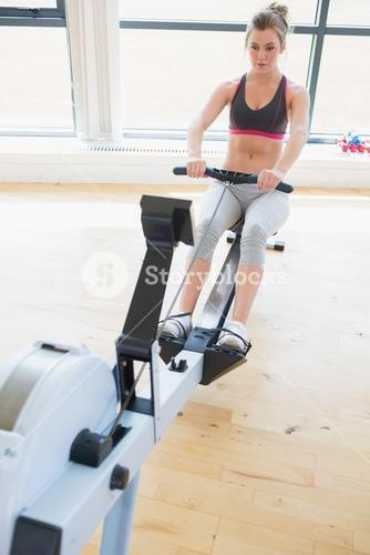 Woman sitting at the row machine pulling