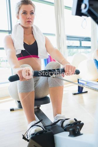 Young woman on the row machine