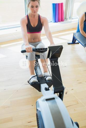 Woman changing settings on row machine