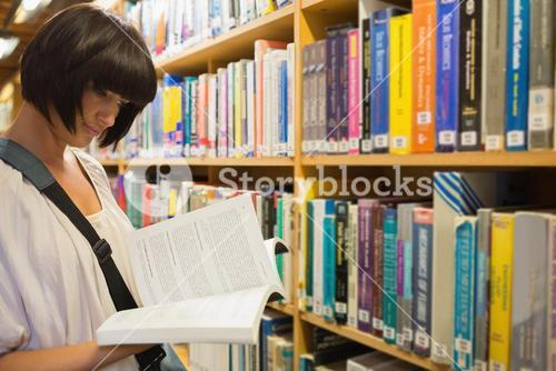 Woman reading a book in front of a shelf