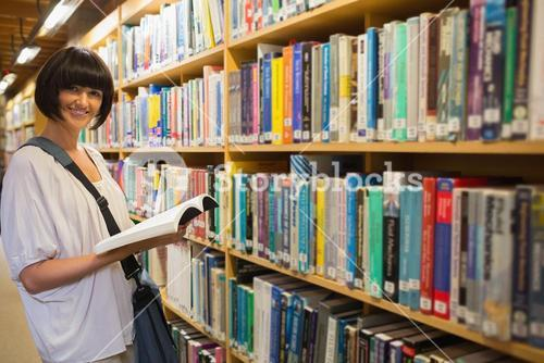 Woman holding a book next to a shelf