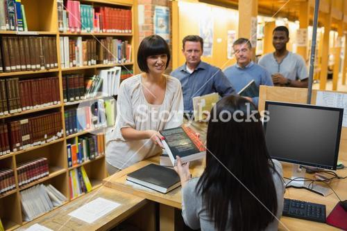 Librarian handing book to woman