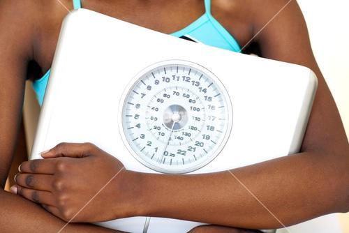 Close up of a fitness woman with thumb up holding a weight scale